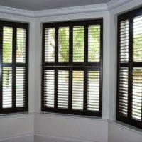 dark tier on tier shutters in bay window