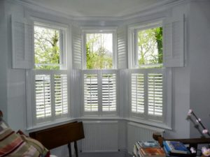 tier on tier shutters in bay window of a reception room